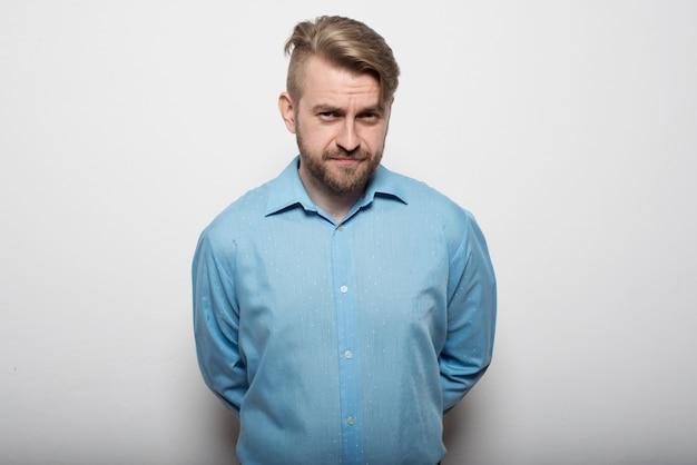 Hübscher junger mann in einem blauen hemd, das an der weißen wand mit verschränkten armen hinter seinem rücken steht