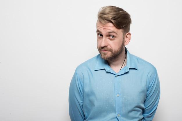 Hübscher junger mann in einem blauen hemd, das an der weißen wand steht