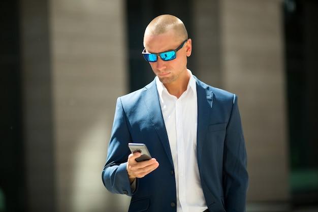 Hübscher junger mann in einem sommeranzug auf einem spaziergang in der sonnenbrille mit einem telefon in der hand