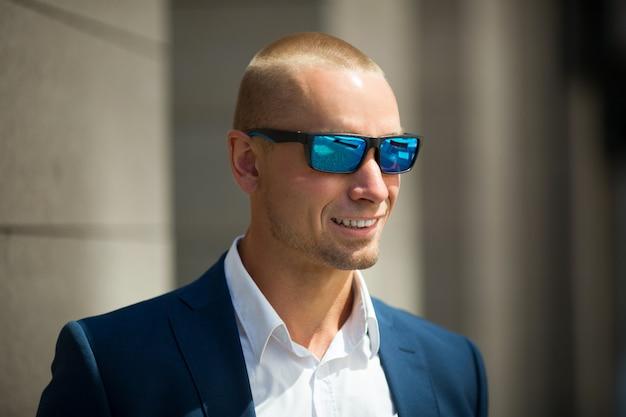 Hübscher junger mann in einem sommeranzug auf einem spaziergang in der sonnenbrille