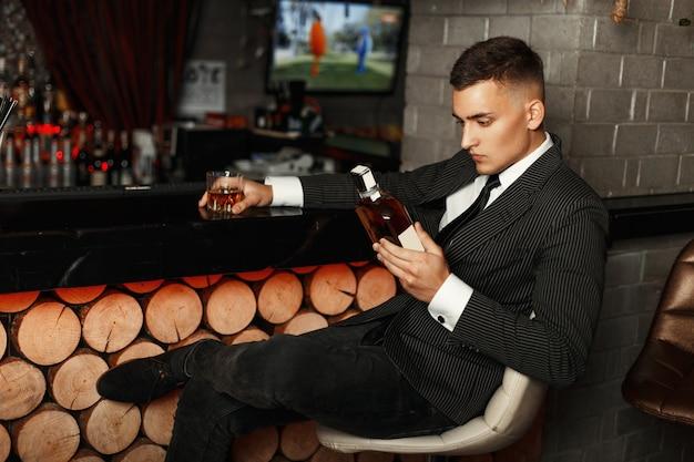 Hübscher junger mann in einem stilvollen anzug, der eine flasche whisky an der bar hält