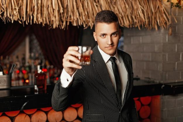 Hübscher junger mann in einem stilvollen anzug, der whisky in der bar trinkt