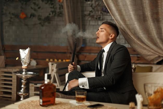 Hübscher junger mann in einem teuren kleid raucht eine wasserpfeife