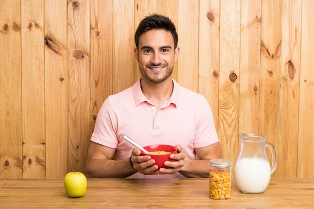 Hübscher junger mann in einer küche, die frühstückt