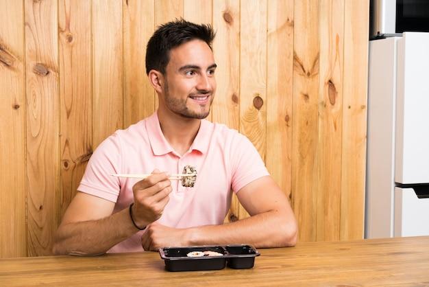 Hübscher junger mann in einer küche mit sushi