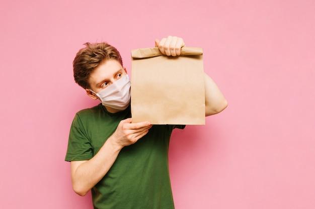 Hübscher junger mann in einer medizinischen schutzmaske steht auf einem rosa mit einer packung lebensmittel von der lieferung. lieferung unter quarantäne.