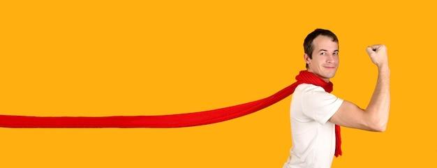 Hübscher junger mann in einer superman-pose, die einen roten fliegenden schal trägt. studioaufnahme auf gelbem grund. werbebanner-modell.