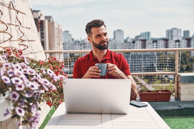 Hübscher junger mann in freizeitkleidung mit laptop und lächelnd beim sitzen auf der dachterrasse sitting