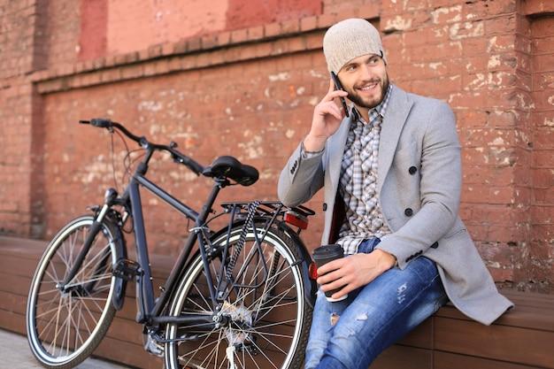 Hübscher junger mann in grauem mantel und hut, der am handy spricht und lächelt, während er draußen in der nähe seines fahrrads sitzt.