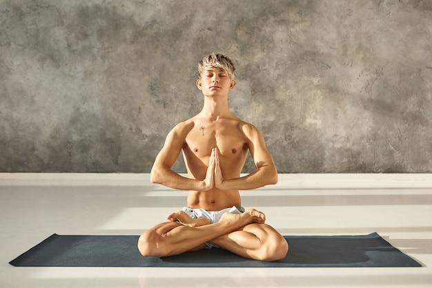 Hübscher junger mann mit blonden haaren und tätowierung auf nacktem oberkörper, der auf yogamatte in lotushaltung sitzt, sukhasana tut, augen schließt und hände in namaste zusammenpresst. meditation und konzentration