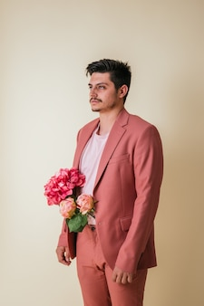 Hübscher junger mann mit blumen in seiner hose, einen rosa anzug tragend