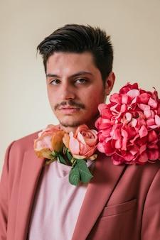 Hübscher junger mann mit blumen um den hals, einen rosa anzug tragend