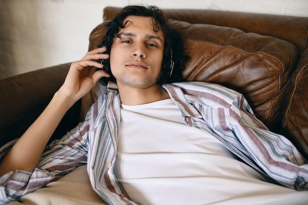 Hübscher junger mann mit borsten, die auf ledersofa liegen, das neue titel online über musik-streaming-dienst unter verwendung der kabellosen kopfhörer hört und entspannten blick hat.