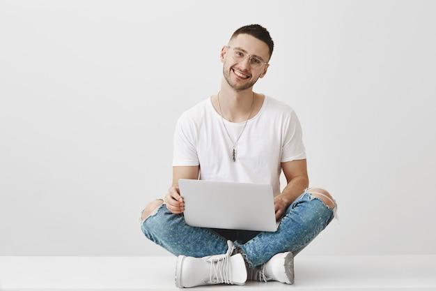 Hübscher junger mann mit brille, die mit seinem laptop aufwirft