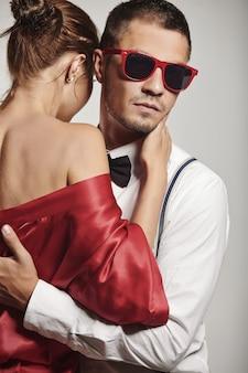 Hübscher junger mann mit der modernen sonnenbrille, die mit mädchen aufwirft