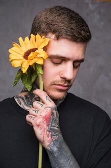 Hübscher junger mann mit der nase durchbohrt, sonnenblume in der hand halten gegen grauen hintergrund