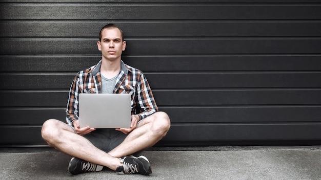 Hübscher junger mann mit einem laptop, der auf dem boden gegen graue wand sitzt.