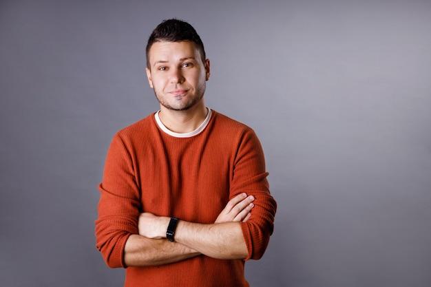 Hübscher junger mann mit einem orangefarbenen pullover