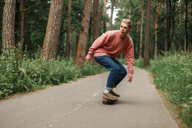 Hübscher junger mann mit einer frisur, die auf skateboard im park reitet