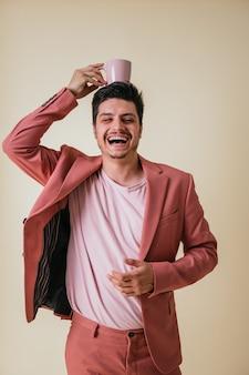 Hübscher junger mann mit einer rosa tasse auf seinem kopf, gekleidet in einen rosa anzug und ein hemd