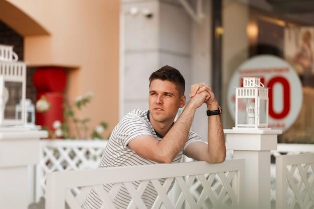 Hübscher junger mann mit einer stilvollen frisur in einem trendigen gestreiften t-shirt steht in der nähe eines vintage-holzzauns