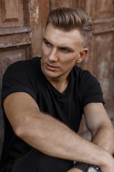 Hübscher junger mann mit frisur im schwarzen t-shirt, das nahe einer alten weinlese-tür sitzt