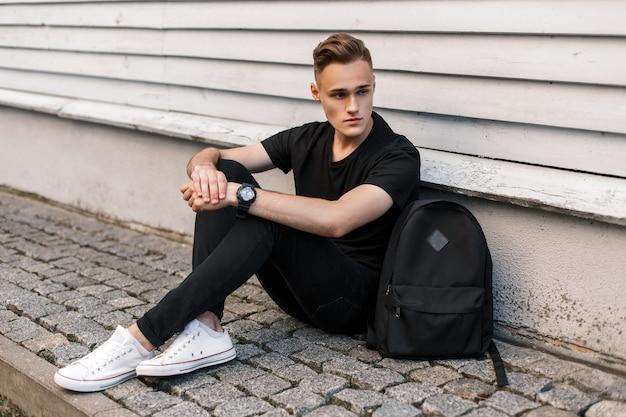 Hübscher junger mann mit frisur in schwarzer modischer kleidung sitzt nahe holzwand und schaut seitwärts