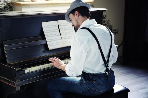 Hübscher junger mann mit hut, der klaviermusik macht