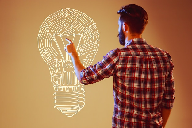 Hübscher junger mann mit ideenbirne auf abstraktem lampenhintergrund. konzept neue idee