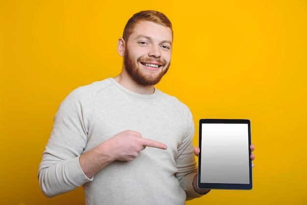 Hübscher junger mann mit ingwerbart lächelnd und kamera betrachtend