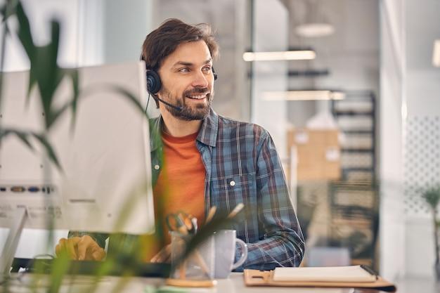 Hübscher junger mann mit kopfhörer, der wegschaut und lächelt, während er den computer bei der arbeit benutzt