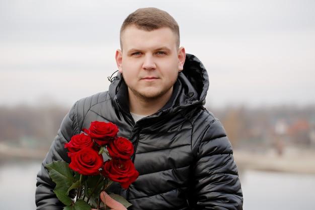 Hübscher junger mann mit roten rosen in den händen draußen bei schneebedecktem wetter