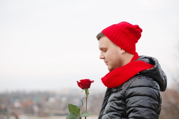 Hübscher junger mann mit roter rose in den händen draußen bei schneebedecktem wetter