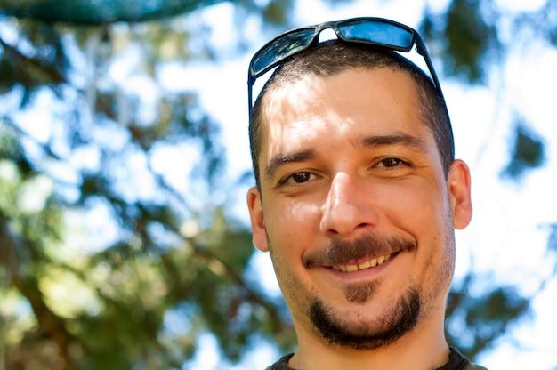 Hübscher junger mann mit schnurrbart und bart und sonnenbrille im park genießend