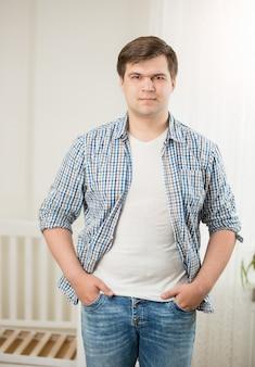 Hübscher junger mann posiert gegen zerlegtes babybett im kindergarten