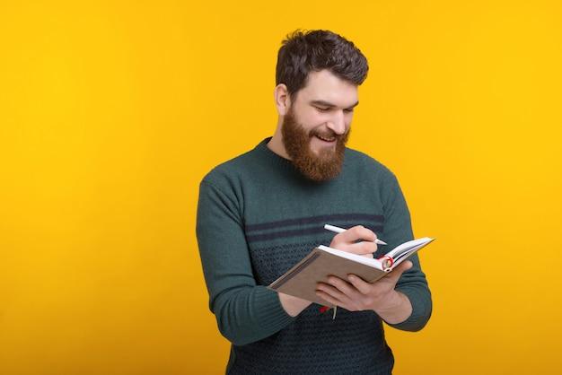 Hübscher junger mann schreibt in die tagesordnung, verwaltet ihre zeit
