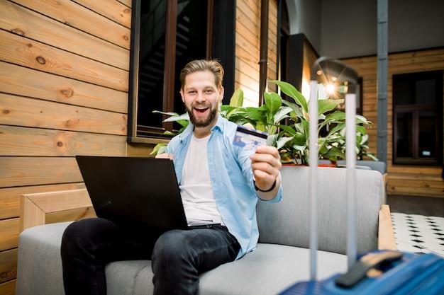 Hübscher junger mann sitzt in der modernen loft-hotelhalle oder in der wartehalle mit laptop und kreditkarte