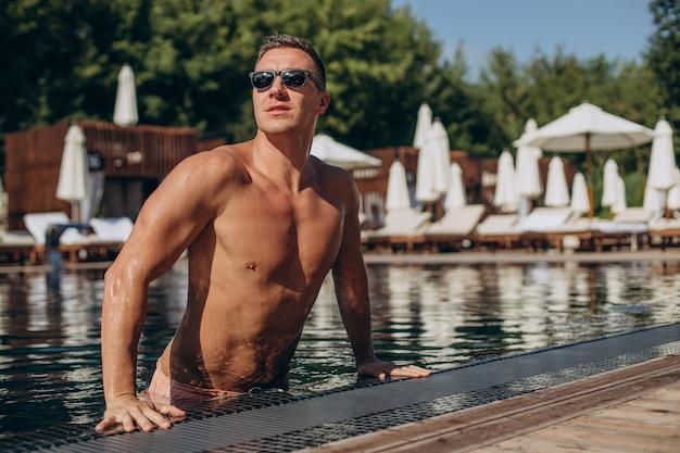 Hübscher junger mann steigt aus dem pool