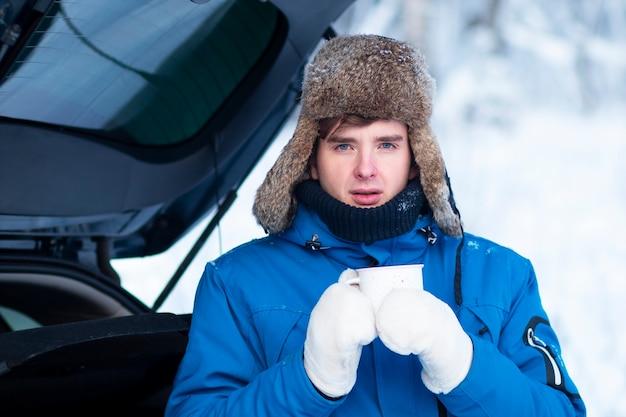 Hübscher junger mann trinkt ein heißes getränk tee oder kaffee aus einer tasse in handschuhen und winterkleidung
