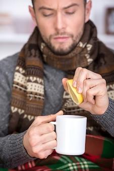 Hübscher junger mann trinkt tee mit zitrone.