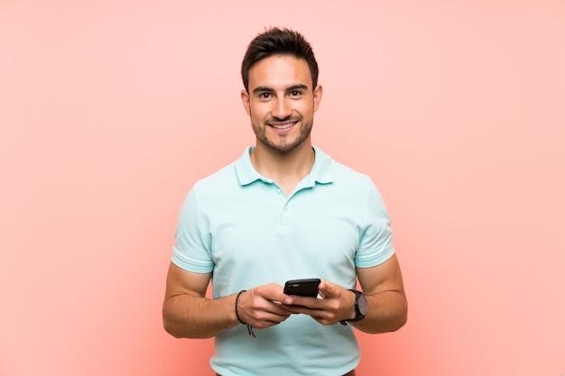 Hübscher junger mann über dem lokalisierten senden einer mitteilung mit dem mobile