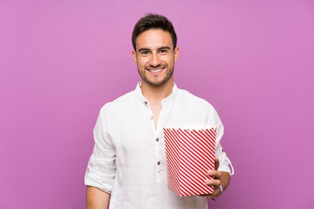 Hübscher junger mann über dem purpur, der popcorn hält