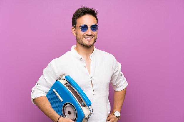 Hübscher junger mann über dem purpurroten hintergrund, der einen radio hält