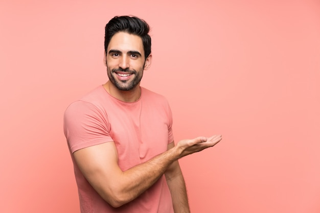 Hübscher junger mann über erweiterungshänden des lokalisierten rosa hintergrundes zur seite, damit die einladung kommt