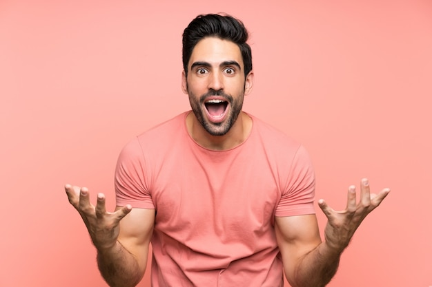 Hübscher junger mann über lokalisiertem rosa unglücklich und mit etwas frustriert
