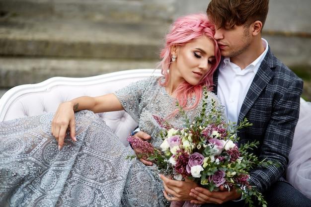 Hübscher junger mann umarmt zarte frau mit dem rosa haar, das auf der weißen couch sitzt