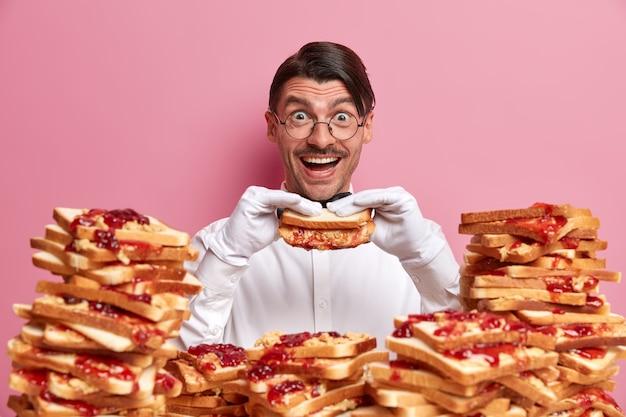 Hübscher junger mann, umgeben von erdnussbutter-gelee-sandwiches