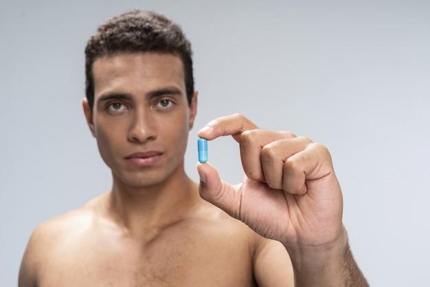 Hübscher junger mann wird eine pille nehmen, die er hält