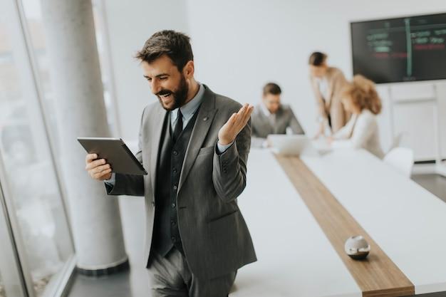 Hübscher junger moderner geschäftsmann mit digitalem tablet im büro