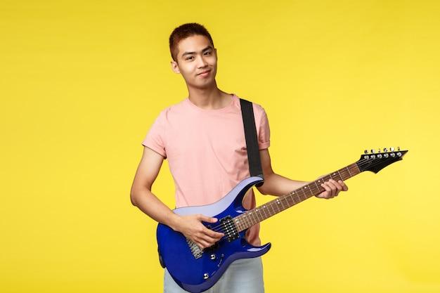 Hübscher junger musiker, der die gitarre spielt und, lokalisiert singt